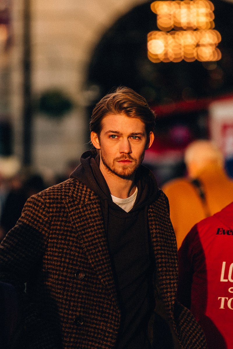 Captured out and about, Joe Alwyn dons an Incotex houndstooth coat, Fendi hoodie, and Mr P. t-shirt.