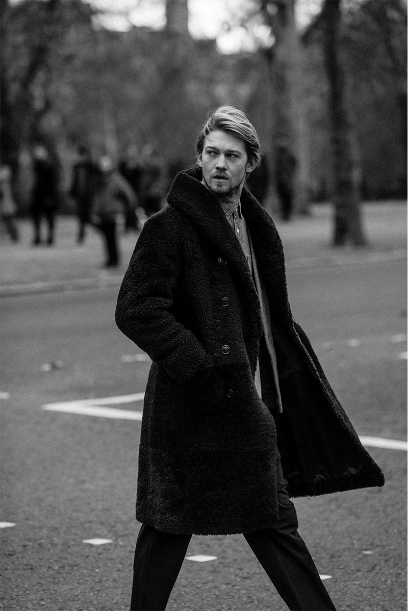 Out for a stroll, Joe Alwyn wears a RRL shearling coat, Visvim wool cardigan, Frame chambray shirt, and Barena trousers.