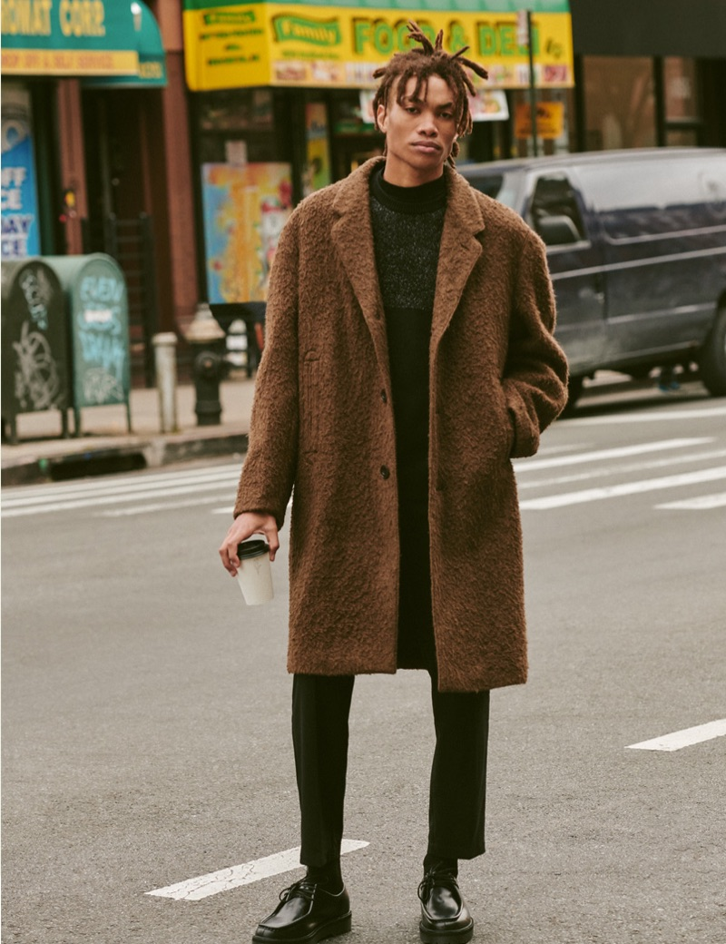 Seth Hill dons a Ted Baker sweater, Lemaire coat, Stüssy cropped trousers, Theory mock tee, and Saturdays NYC shoes.