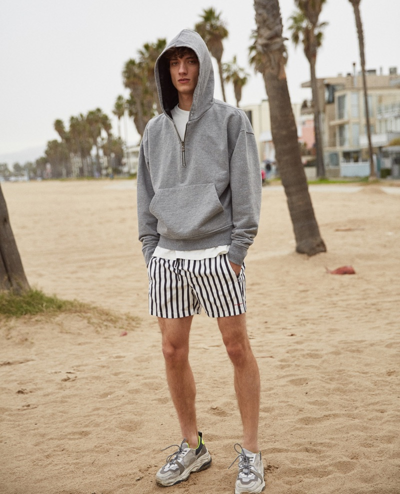 Serge Rigvava hits the beach in striped swim shorts by The Kooples.