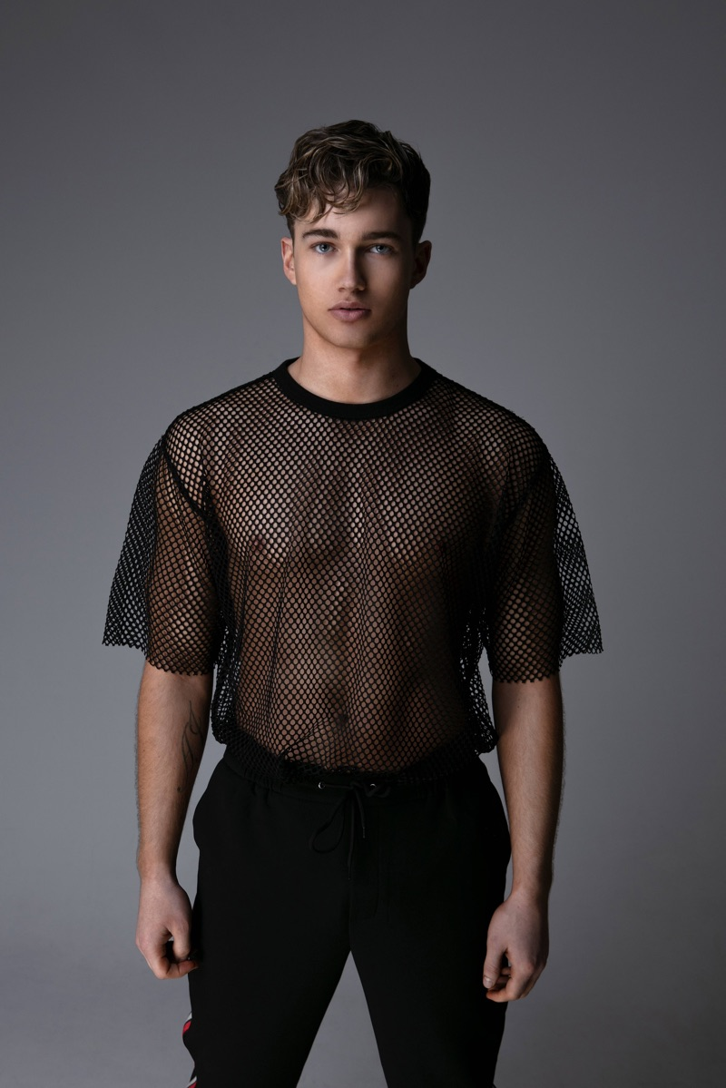 Connecting with Gay Times, AJ Pritchard rocks an oversized mesh tee.