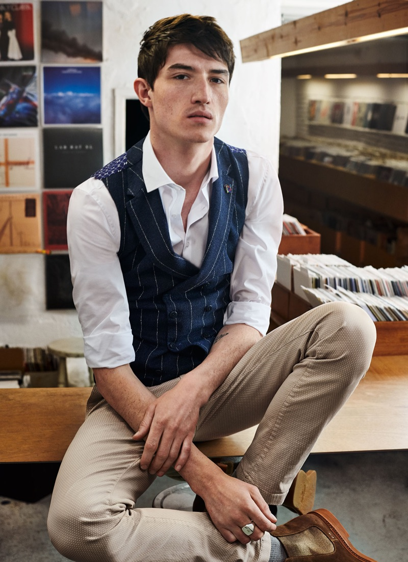 Inspiring in a smart look, Jester White wears a Digel Move shirt, pinstriped vest, and slim-fit pants.