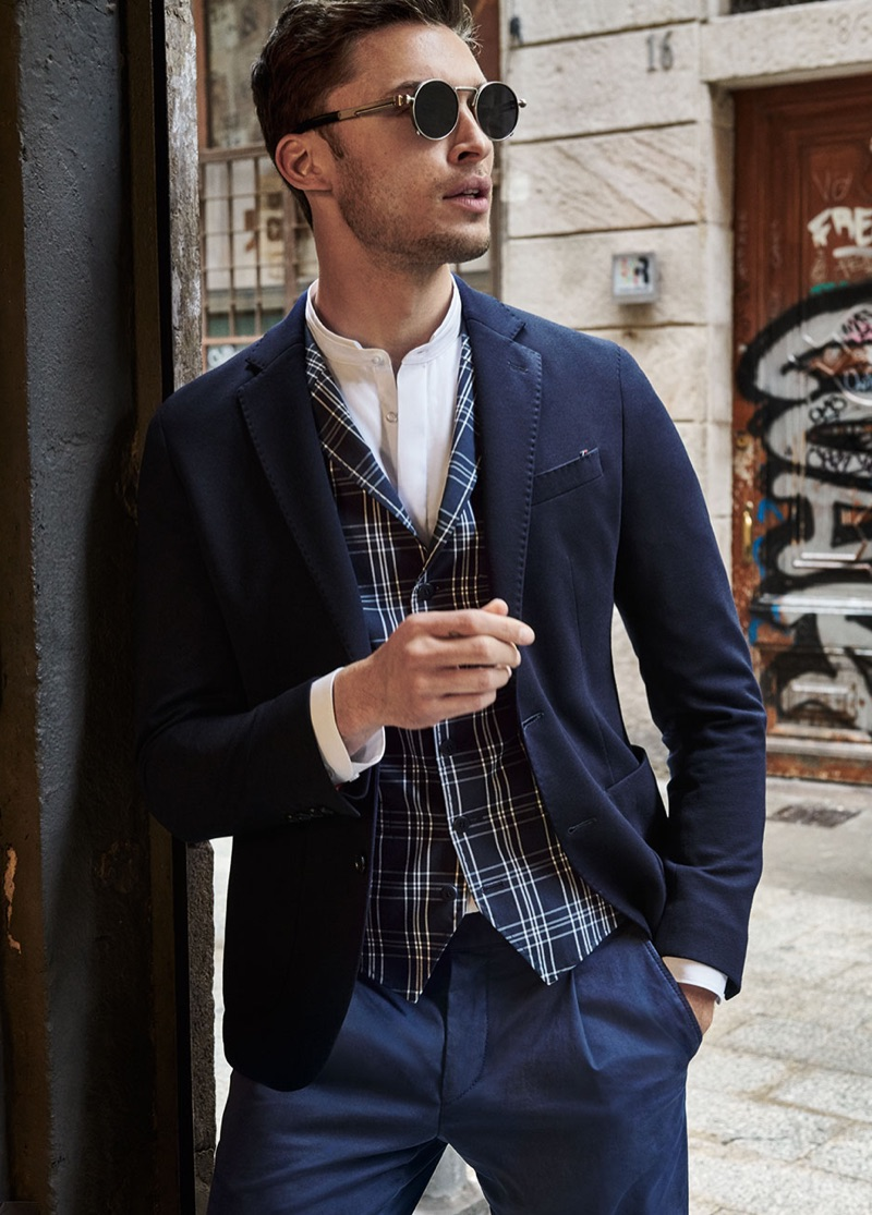 British model Harvey Haydon dons a navy blazer, check waistcoat, and pleated pants from Digel Move.