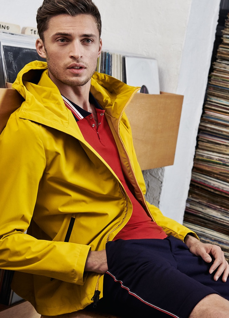 Wearing yellow, Harvey Haydon models a jacket with a red polo and navy shorts by Digel Move.