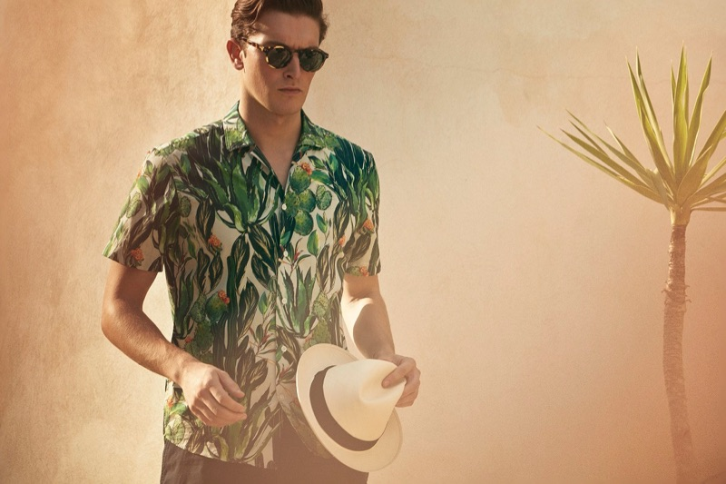 Embracing a tropical vibe, Oli Lacey sports a short-sleeve printed shirt for Gieves & Hawkes' spring-summer 2019 campaign.