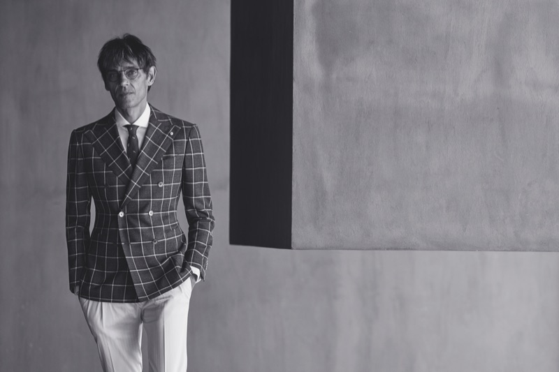 Sporting glasses, Didier Vinson wears a windowpane print double-breasted jacket from Luigi Bianchi Mantova.