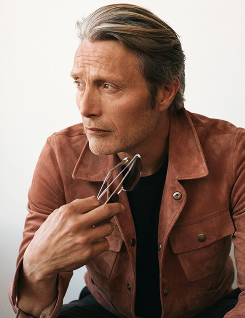 Actor Mads Mikkelsen sports a Tom Ford slim-fit suede jacket and t-shirt with Ralph Lauren Purple Label suit trousers and Barton Perreira sunglasses.