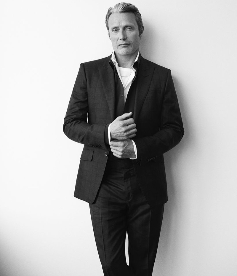 Front and center, Mads Mikkelsen wears a Tom Ford shirt, t-shirt, suit jacket and trousers with a Berluti shirt and Givenchy necklace.