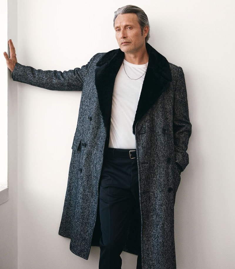 Connecting with Mr Porter, Mads Mikkelsen sports a Dunhill herringbone coat, Tom Ford t-shirt, Berluti trousers, Loro Piana suede belt, and Saint Laurent necklace.
