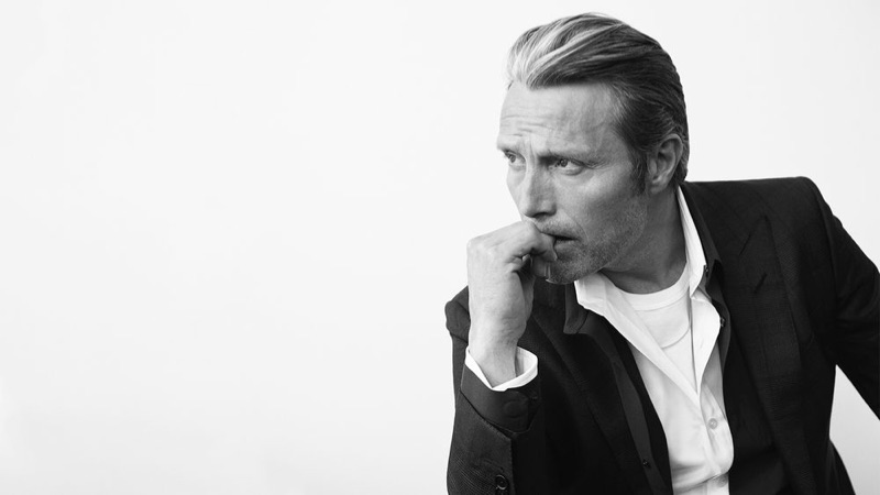 Mads Mikkelsen dons a Tom Ford t-shirt, shirt, and suit jacket with a black Berluti shirt.