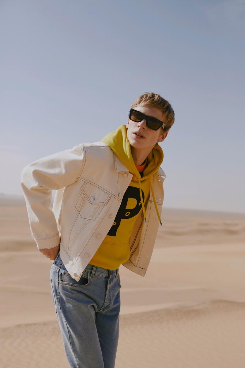 Fluoro: Robbi Gruendler rocks a Helmut Lang denim trucker jacket, Albam striped t-shirt, and a Pop Trading Company fluoro logo hoodie.