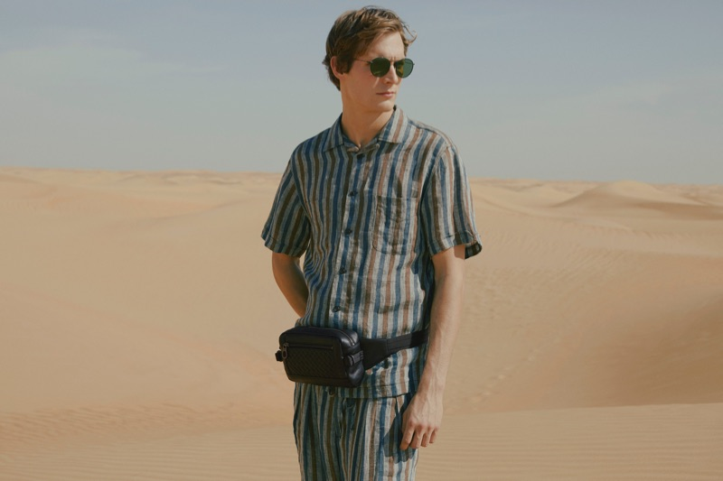 Small Bags: Felix Gesnouin wears a striped camp-collar linen shirt and trousers by Monitaly with a Bottega Veneta leather belt bag and Oliver Peoples sunglasses.