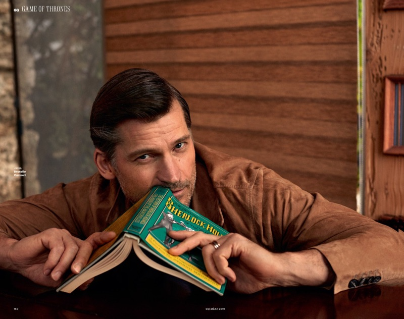 Reading a book, Nikolaj Coster-Waldau sports Brunello Cucinelli.