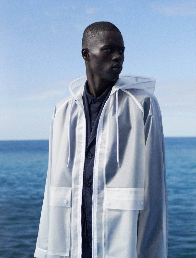 Model Alpha Dia wears a translucent white hooded jacket by Reserved.