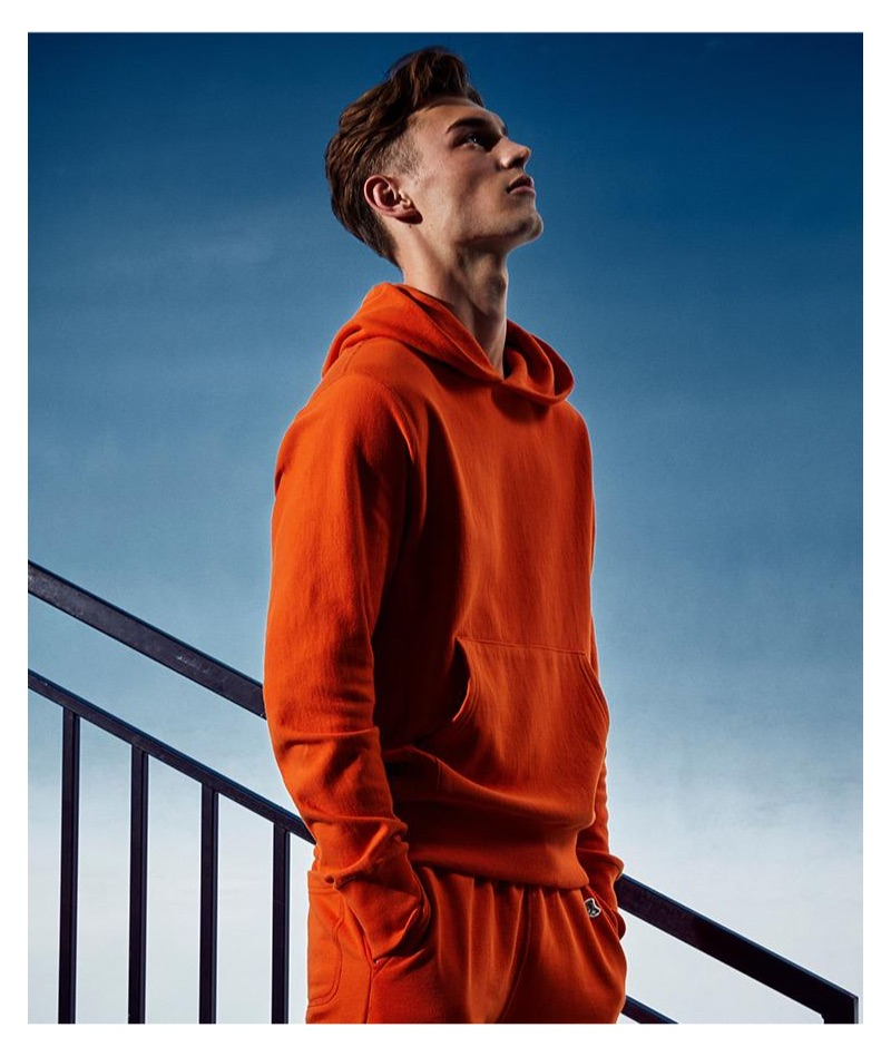 Kit Butler sports an orange Todd Snyder + Champion terry hoodie and jogger sweatpants.