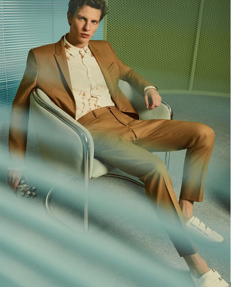 Tim Schuhmacher dons a trim tailored brown suit by Zara Man.