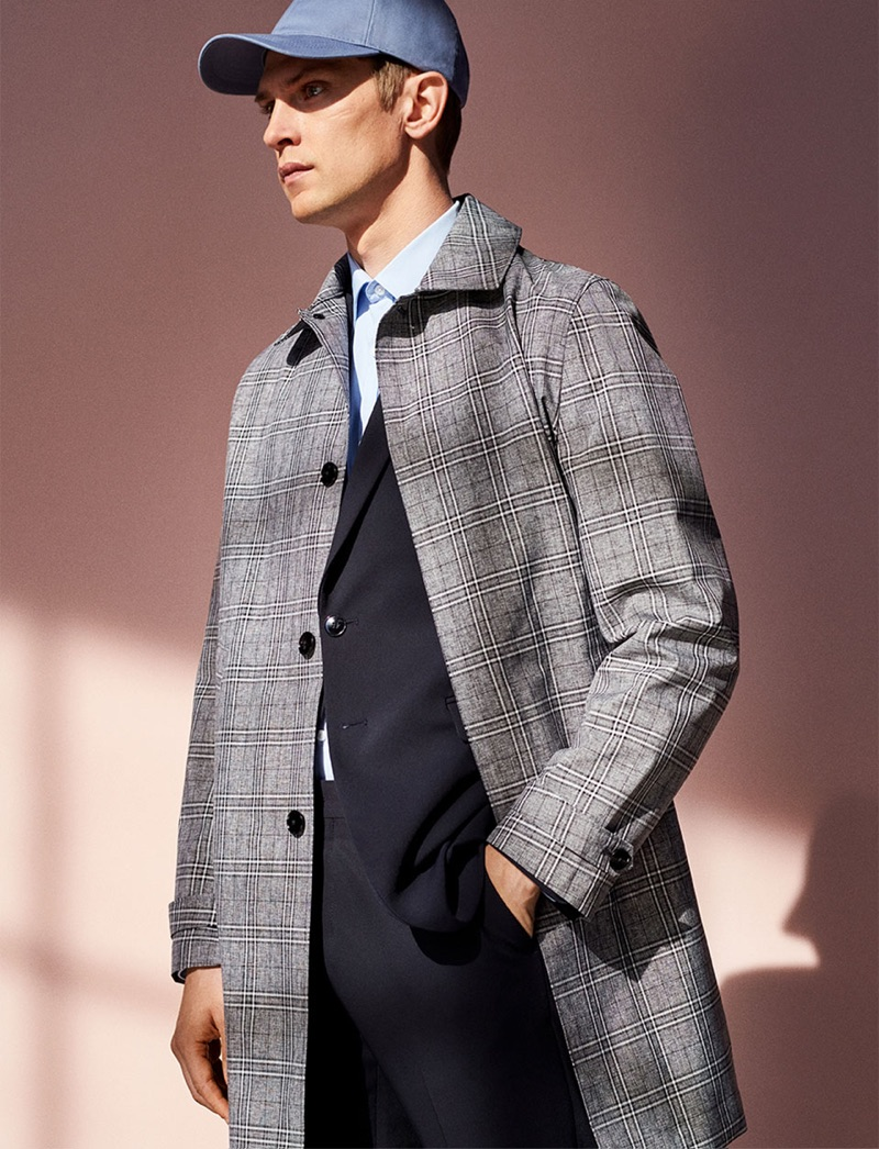 A sleek vision, Mathias Lauridsen wears a checked coat with a suit and cap.