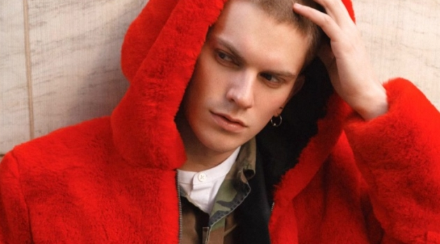 Starring in a series of images, Alexander Morel models a red fur jacket by PEACEMINUSONE with a Stüssy camouflage print jacket, Prada trousers, Fila sneakers and a Ralph Lauren shirt.