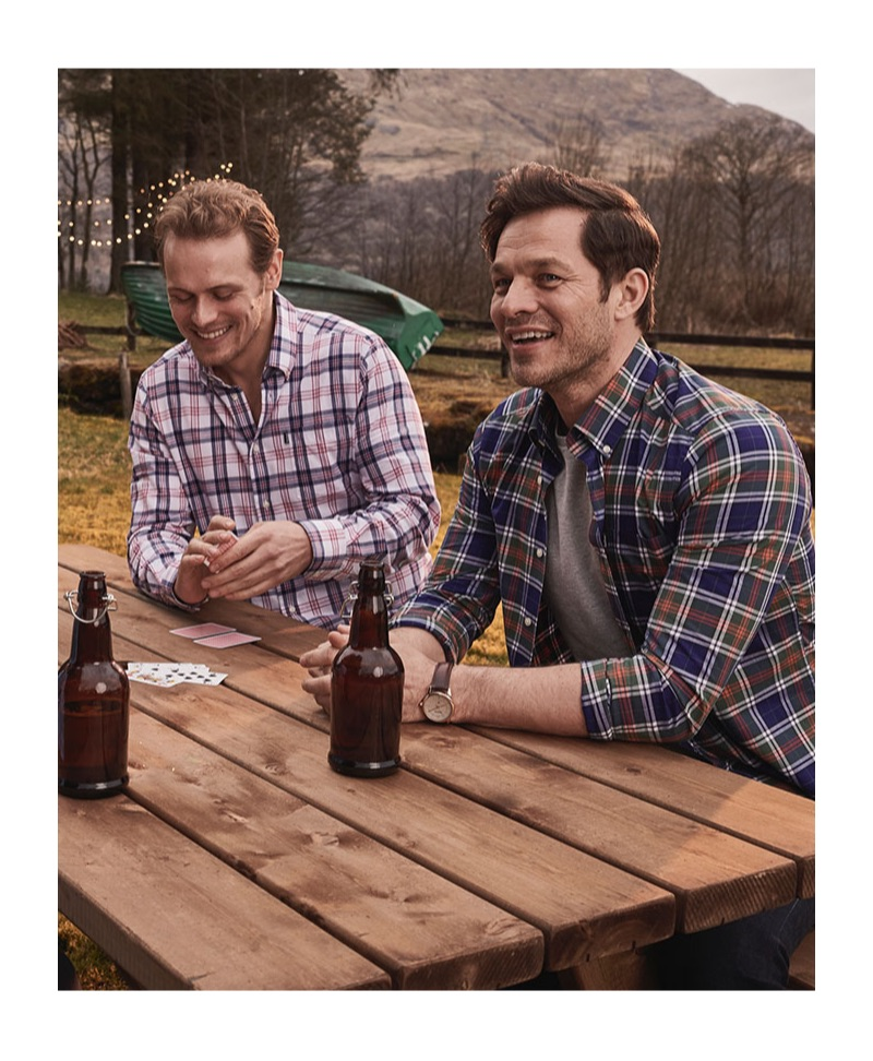 Sporting plaid shirts by Barbour, Sam Heughan and Paul Sculfor sit down for drinks.