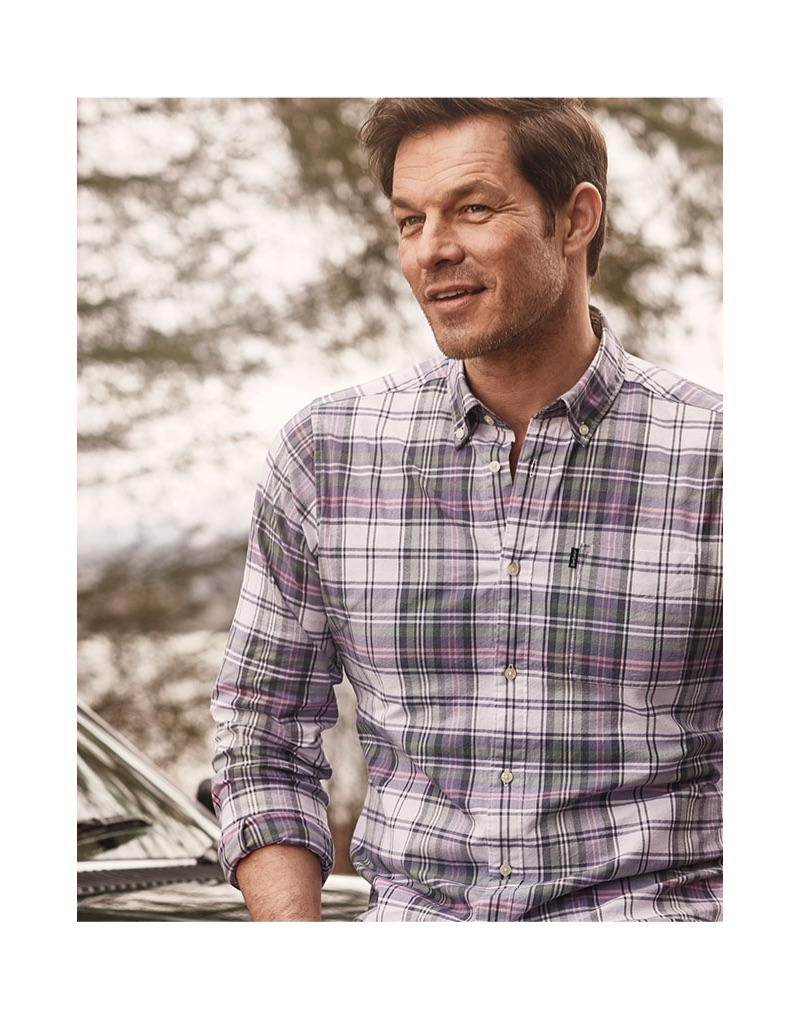 All smiles, Paul Sculfor wears a Barbour plaid shirt from the brand's spring-summer 2019 collection.