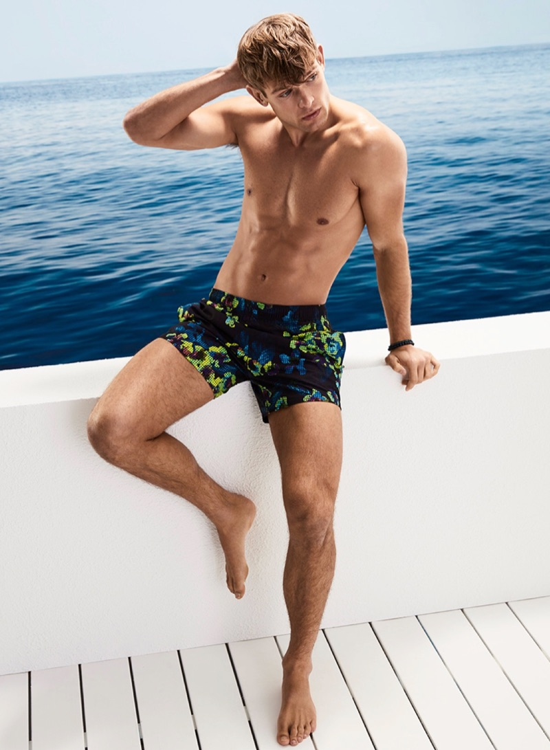 Elliott Reeder models digital flower print swim trunks by BOSS.
