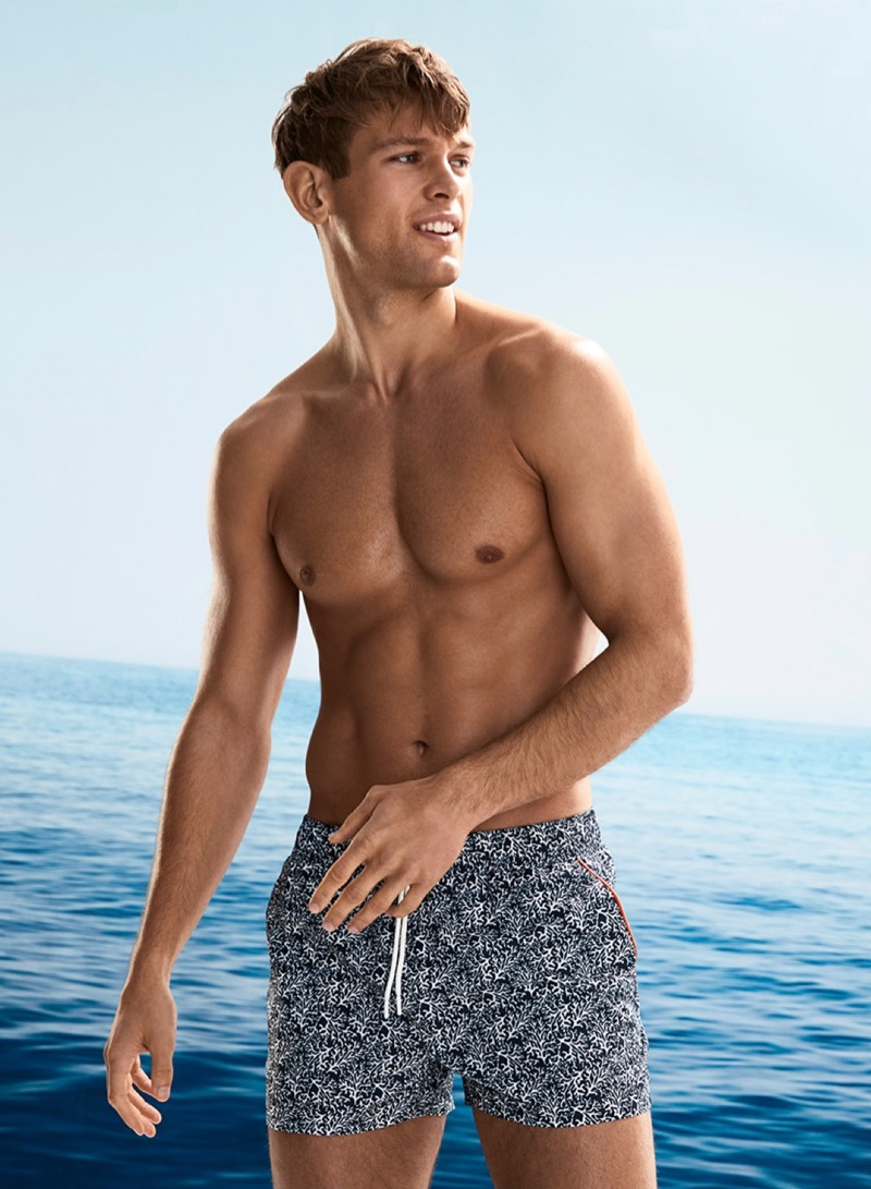 Model Elliott Reeder wears I.FIV5 coral print swim trunks.