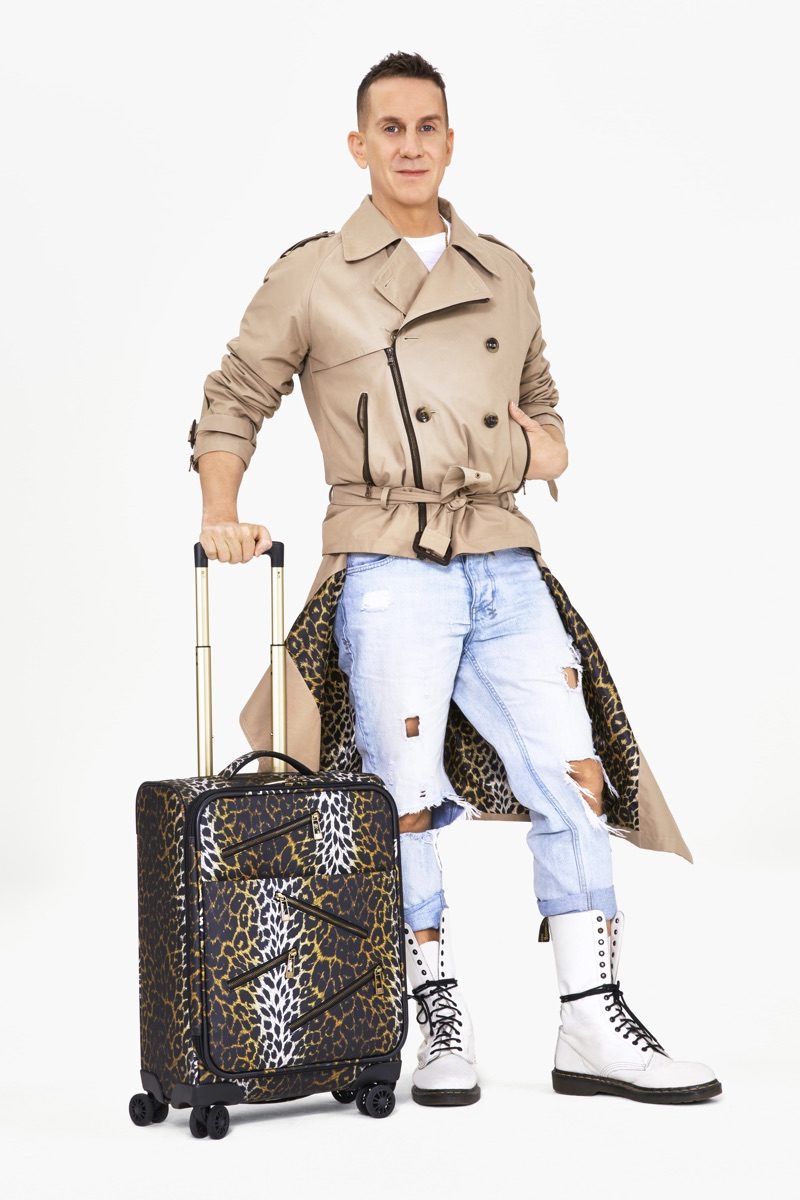 Jeremy Scott poses with luggage from his London Fog collaboration. He also sports a trench coat from the line.
