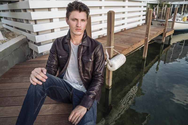 Model Eli Hall is in the spotlight as he dons a leather jacket and jeans from John Varvatos Star USA.