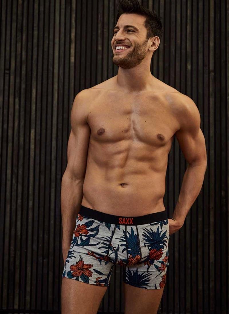 All smiles, Kevin Sampaio wears SAXX tropical print boxer briefs.