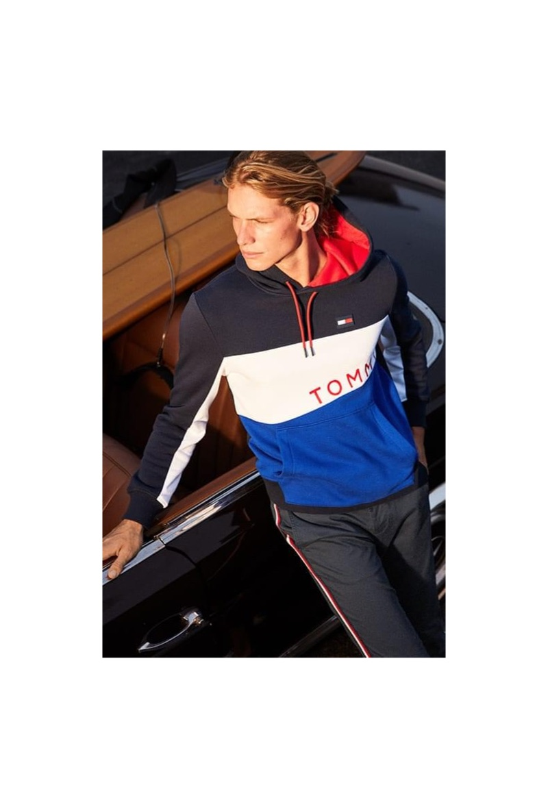 Going sporty, Hunter Bach wears a Tommy Hilfiger colorblocked graphic hoodie and stripe chinos.