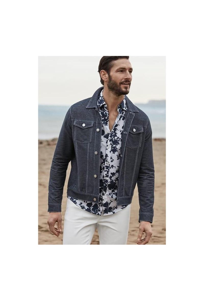 A smart vision, Parker Gregory dons a Michael Kors stretch denim trucker jacket, floral print shirt, and white slim-fit jeans.