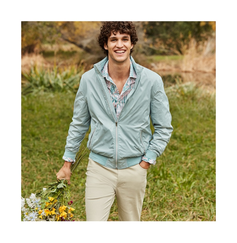 All smiles, Francisco Henriques dons a jacket and printed shirt from Macy's.