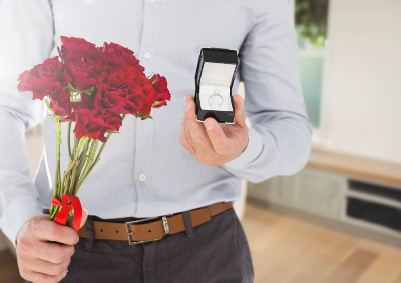 Man Holding Flowers and Diamond Engagement Ring