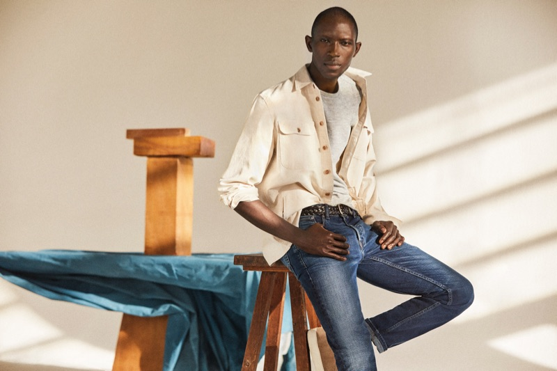 Medium Denim: A chic vision, Armando Cabral wears distressed denim jeans with an off-white oversized shirt.