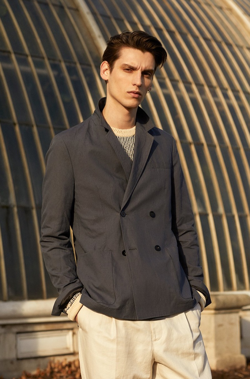 Model Anthony Gilardot sports a double-breasted suit jacket, striped sweater, and trousers from Mr P.