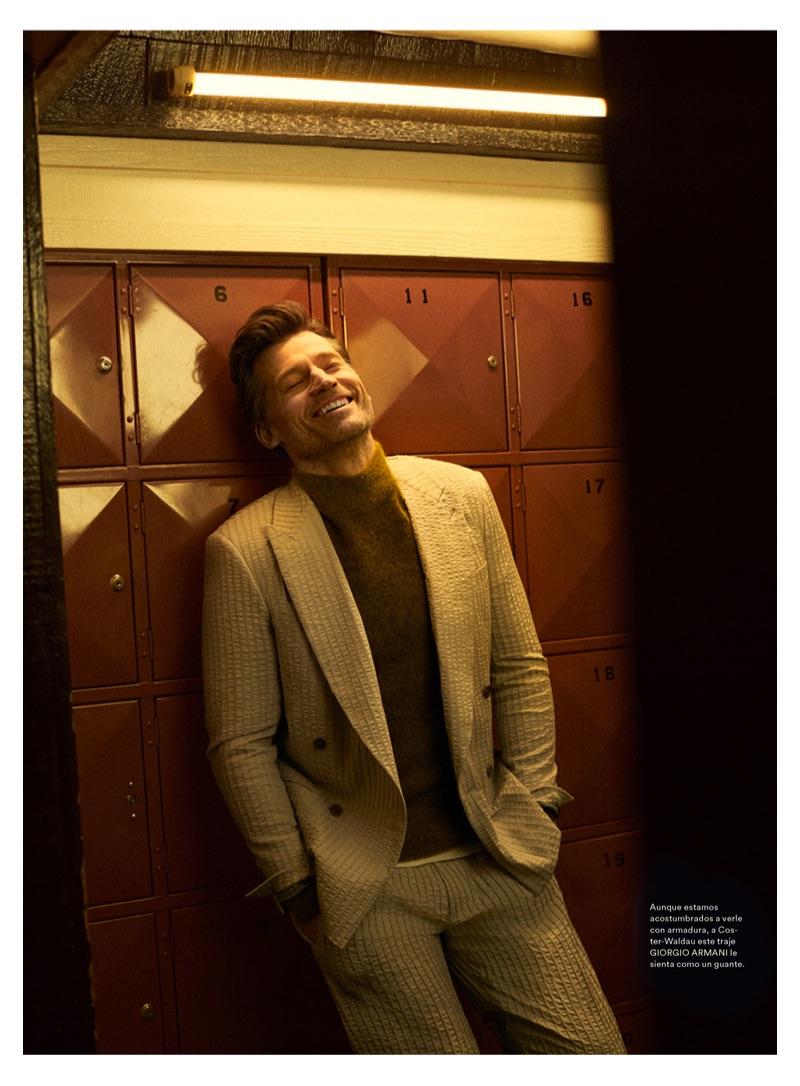 All smiles, Nikolaj Coster-Waldau wears a Giorgio Armani suit and sweater.