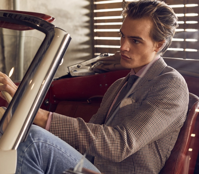 Sitting in a vintage car, Parker van Noord wears a suit jacket with a pair of denim jeans.
