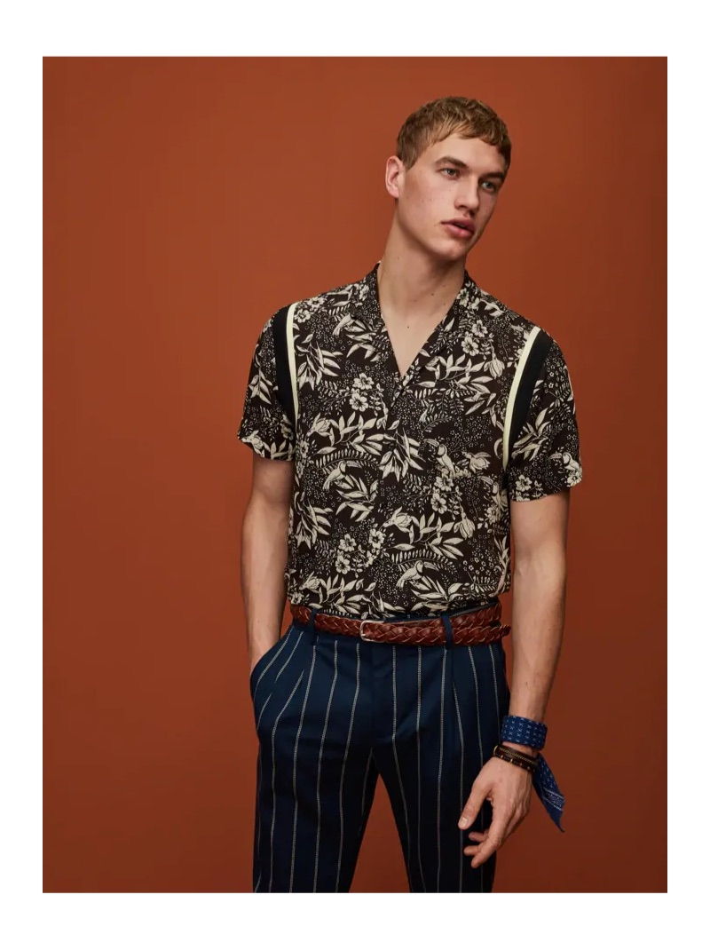 Mixing prints, Paul François wears a Hawaiian print shirt and pinstripe pleated trousers by Scotch & Soda.