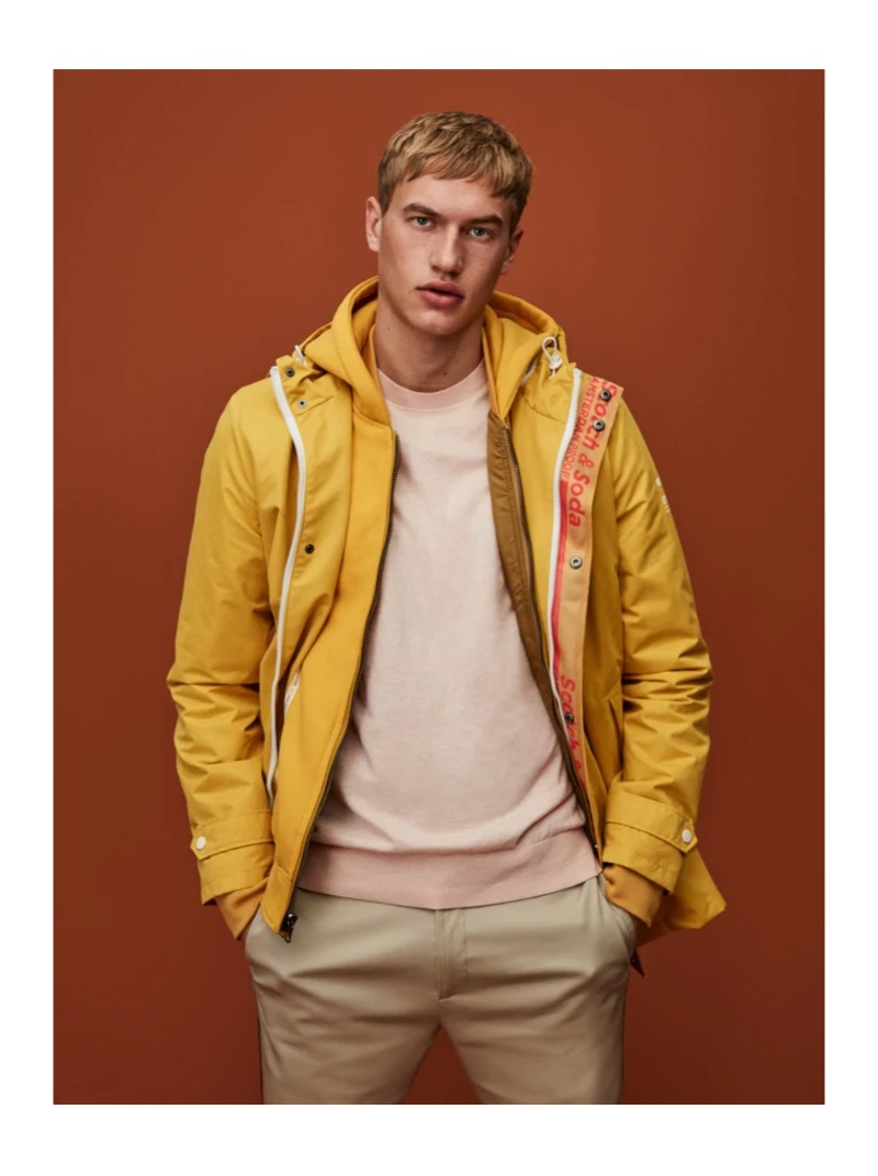 Embracing a pop of color, Paul François wears a yellow rain parka by Scotch & Soda.