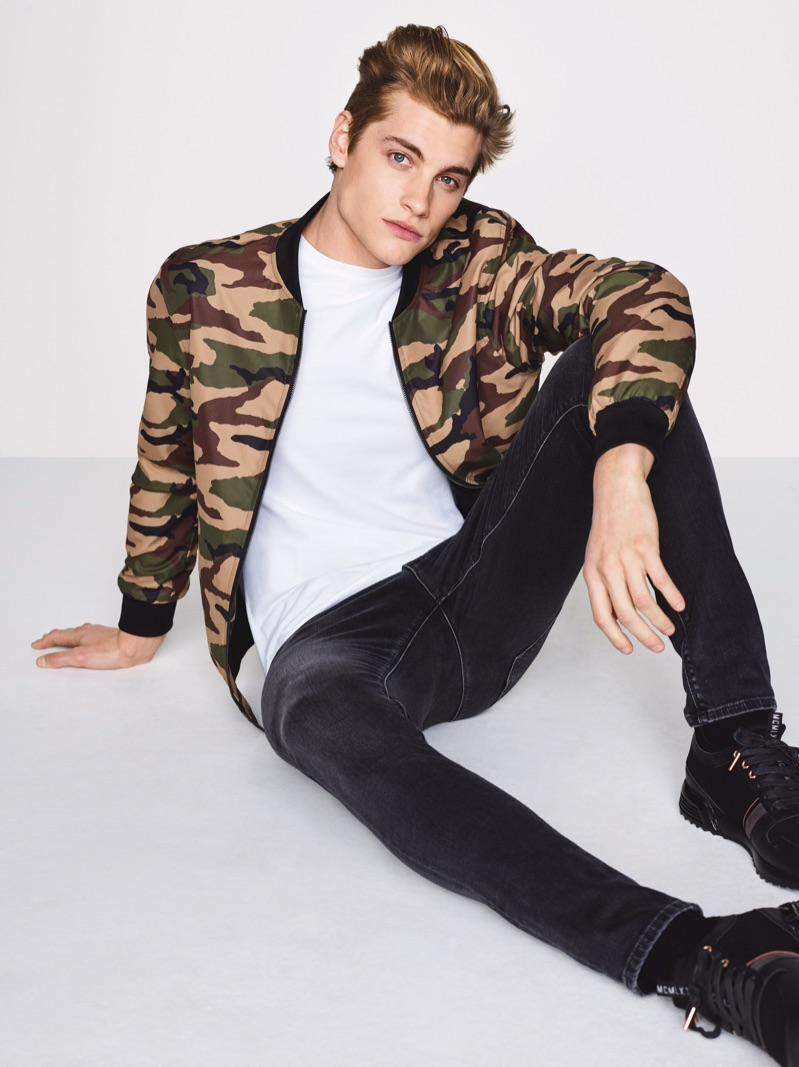 British model Rob Knighton wears a camouflage print bomber jacket with jeans by River Island.