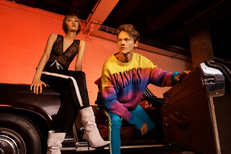 """Embracing bright colors, Ryan Keating dons an AMIRI """"Kisses"""" pullover sweater and track pants."""