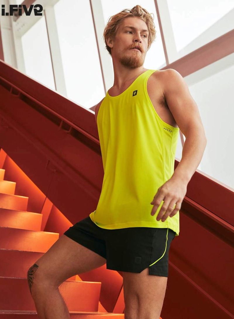 Ready for a workout, Harry Goodwins wears a yellow tank and running shorts by I.FIV5.