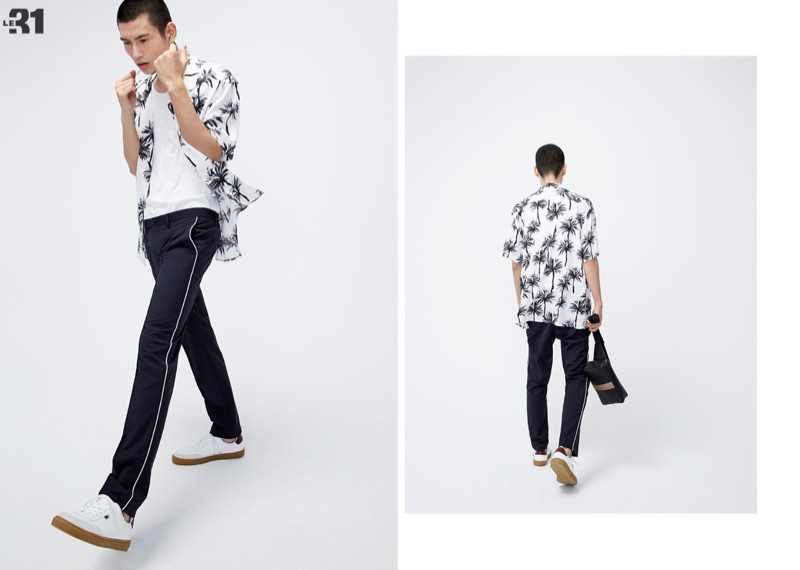 Embracing a cool vibe, Kohei Takabatake rocks a LE 31 printed camp shirt with piped pants, and a loose tank with white Simons leather sneakers.