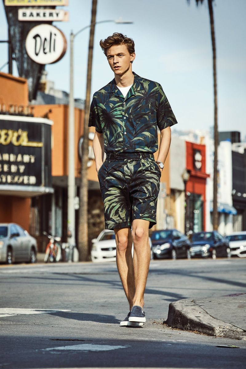 Making a tropical statement, Max Barczak dons a Todd Snyder olive palm print camp collar shirt and shorts.
