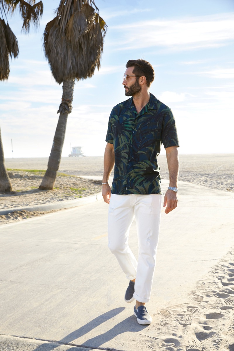 A summer vision, John Halls dons a Todd Snyder cotton camp collar olive palm print shirt and white Japanese selvedge chino officer pants.