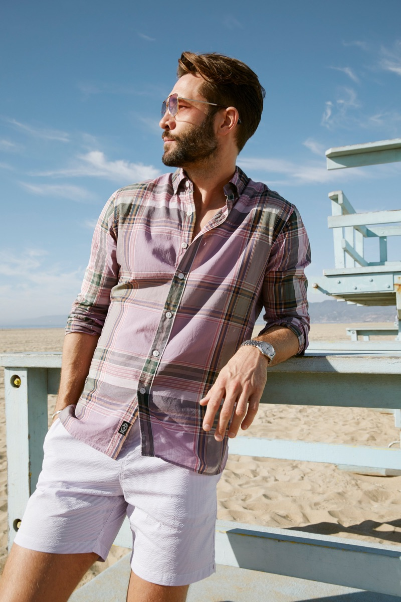 """Model John Halls wears a Todd Snyder lightweight button-down purple Madras shirt and 7"""" weekend stretch shorts in lavender."""