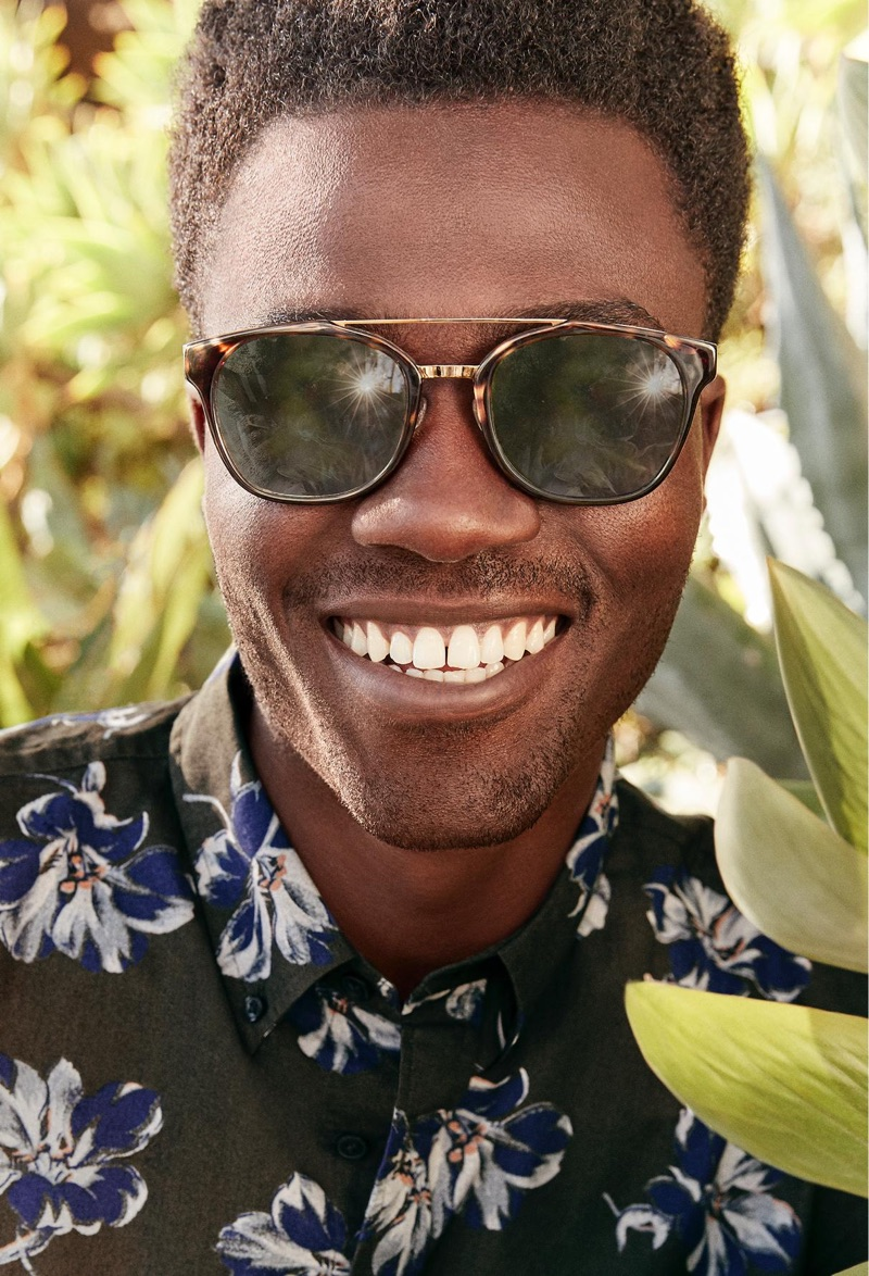 All smiles, Remi Alade-Chester rocks Warby Parker's Fairfax sunglasses in cognac tortoise with polished gold.