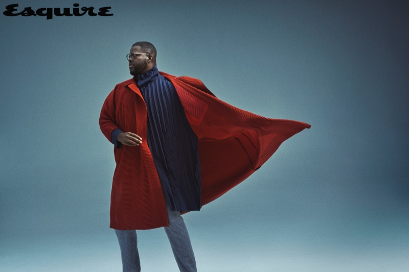 A smart vision, Winston Duke sports a Homme Plissé Issey Miyake overcoat and coat with Issey Miyake Men trousers.