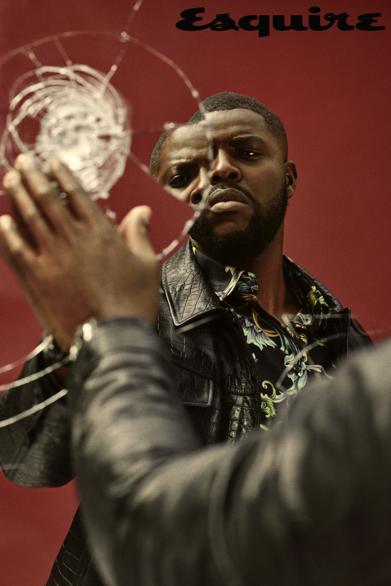 Winston Duke sports a leather jacket by Tom Ford with a Versace shirt.