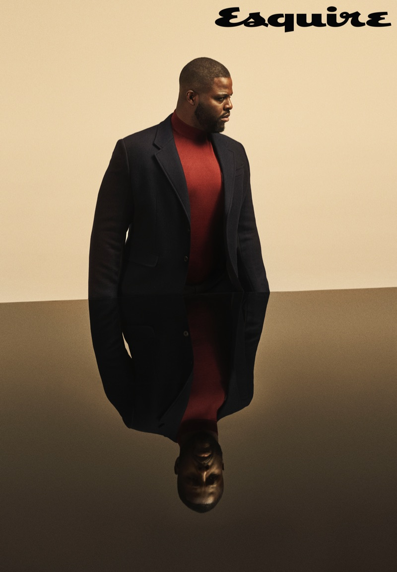 Actor Winston Duke sports a turtleneck, trousers, and jacket by Prada.